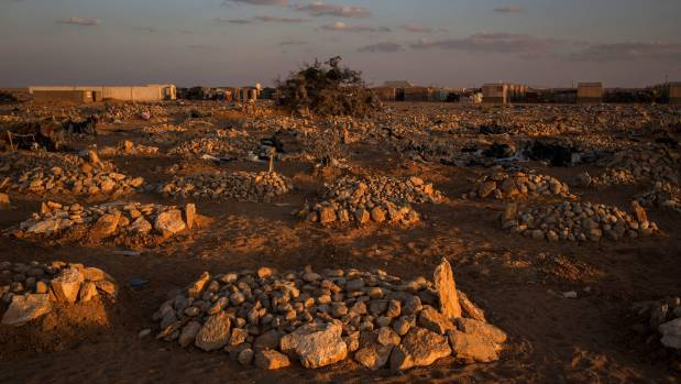 Recently dug graves sit edges of a cemetery at the Shabelle IDP (internally displaced people) camp in Garowe, Somalia.