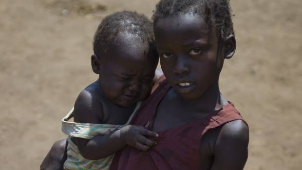 A young girl holds a baby as she stands and waits for a truck to take them to an area where they will be able to set up ...