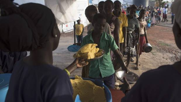 South Sudanese refugee families receive food at the Kuluba Collection Point in Uganda.