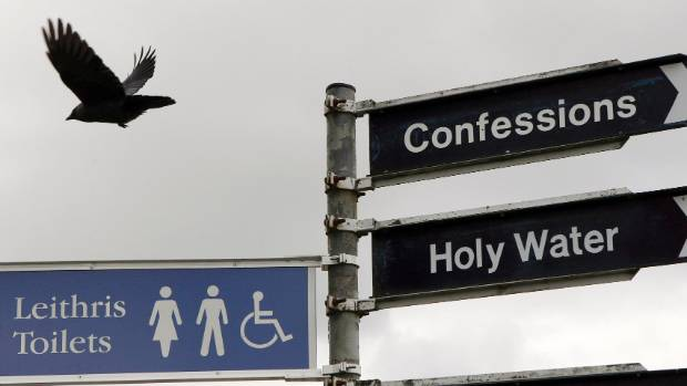 Signposts point the way to toilets, the hearing of Confessions and the location to collect Holy Water in the village of ...