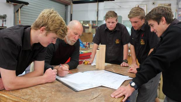 Teacher Jeff Harnish goes through the plans with students  Dean Richardson, Connor Hodgison, Ben  Parrott and Caleb Smith.