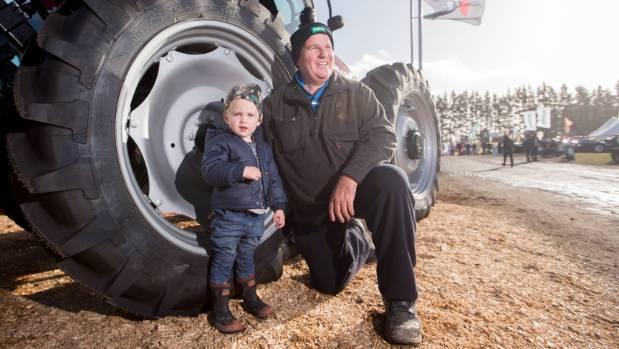 Waiuku dairy farmer Stephen Roubos and his grandson Oliver Forbes-Roubos, 2, exploring the tractors at the Fieldays.