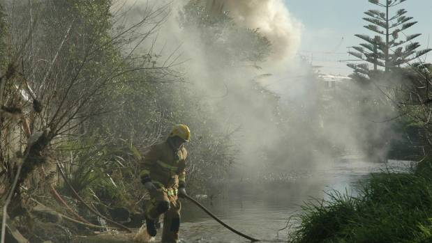 A Porirua firefighter drags a hose through the Porirua stream to gain access to the scrub fire at the northern end of ...