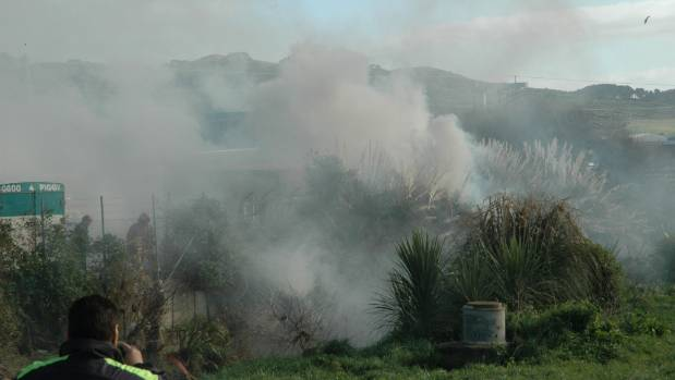 A bystander watches as firefighters try to gain better access to a scrub fire that rages at the northern end of Porirua ...