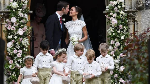 Pippa Middleton kisses her new husband James Matthews as the bridesmaids and pageboys walk ahead on May 20, 2017 in ...