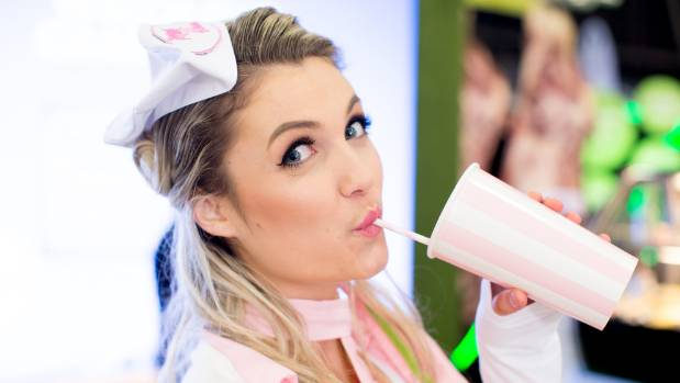 Erin Wells takes a drink from a sheep shake, on the menu at Fieldays 2017.