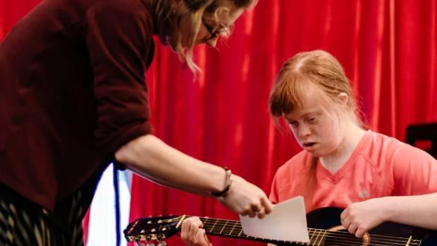 Hutt Timebank's Victoria Thompson (left) teaches Mayana Mahoney Hall to play the guitar.