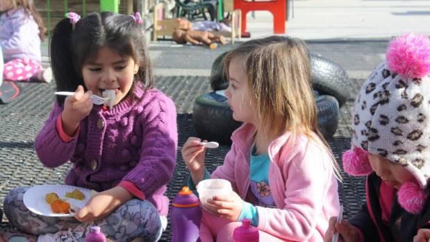 Uptown Preschool children Cristina Fernandez-Puertas, left, and Amelia Old enjoy the hangi.