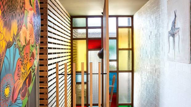 Stained glass panels bring colour to the stairwell leading down to the media room, laundry and guest suite; this ...
