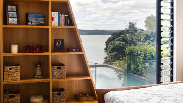 The bookshelf in the master bedroom echoes the slope of the zinc-wrapped form of the living block that lies beyond the ...