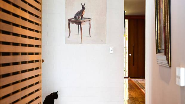 Sooty the cat sits beneath an oil painting of a rabbit by Finnish artist Silja Selonen.