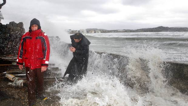 Chas Brown, left, and Lyal Reedy get a drenching as waves crash over Queens Drive, Lyall Bay, at high tide after a storm ...