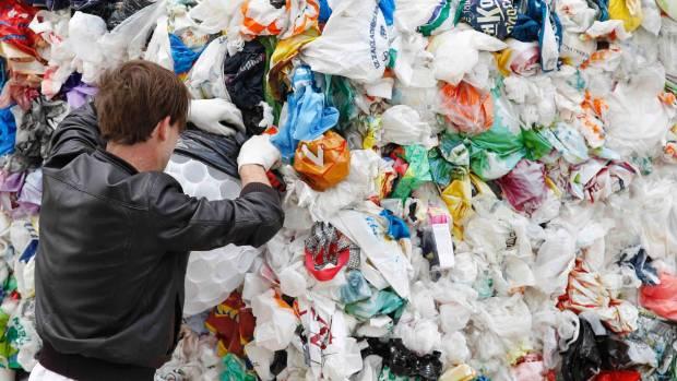 "Slovenian artist Miha Artnak works on his ""Plastic Bag Monster"" outside the European Commission headquarters in Brussels."