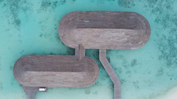 The overwater restaurant, with its glass-bottom bar, is a destination in itself.