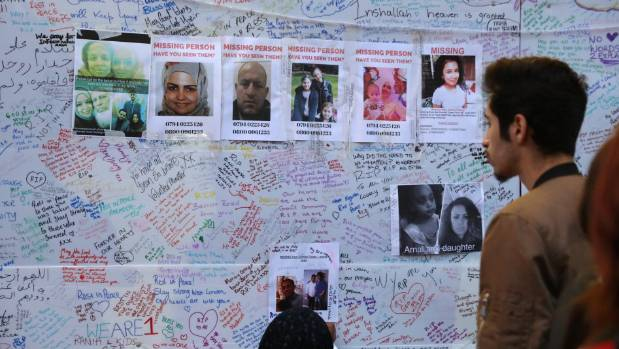 A man looks at a message wall near the Grenfell Tower block in London.