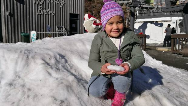 Khloe-Joy Tamihana has fun in the snow mound children can play in for free outside Happy Valley Bistro.