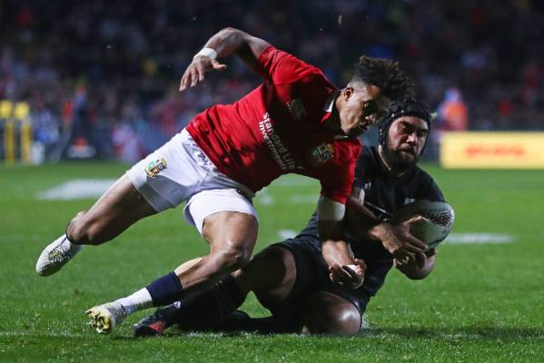 Charlie Ngatai of the NZ Maori cleans up the loose ball under pressure from Anthony Watson of the Lions.