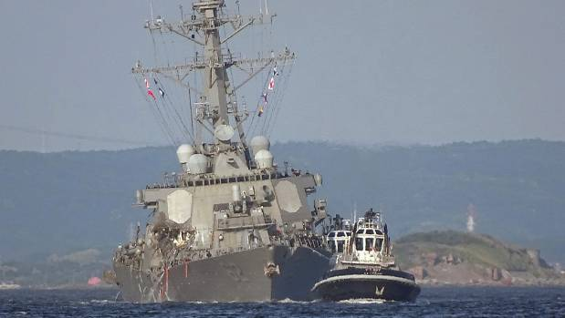 A listing USS Fitzgerald is towed by a tugboat in the waters near the US Naval base in Yokosuka, southwest of Tokyo ...