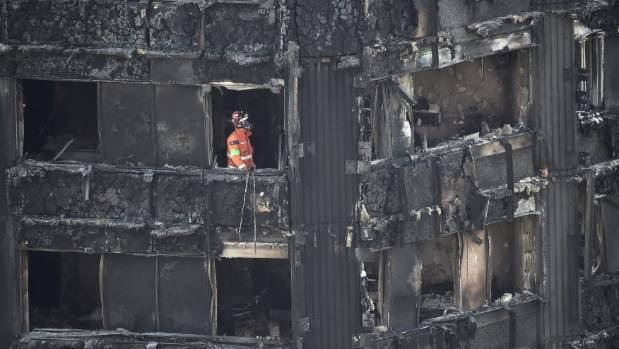 An emergency services worker inside the burnt-out Grenfell apartment tower block in London. At least 58 people were ...