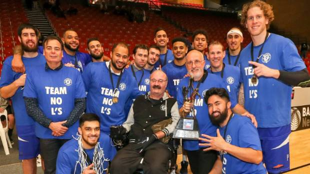 The Wellington Saints celebrate the win with their long-time chairman Justin Toebes (centre).
