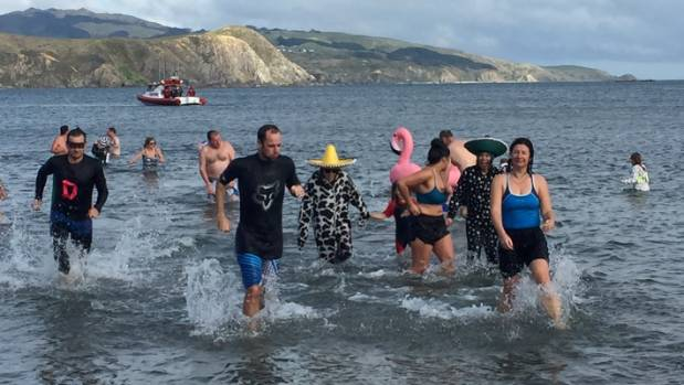 Not wasting time in the freezing water, members of the annual Plimmerton Midwinter Dip head back to shore.