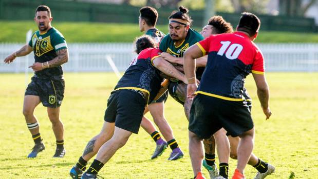 Kia Ora Warriors second rower Te Utanga Tautuhi, centre, runs into a solid line of Tainui Rhinos defence at Fitzherbert ...