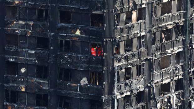 Members of the emergency services work inside burnt out remains of the Grenfell apartment tower in North Kensington, London.