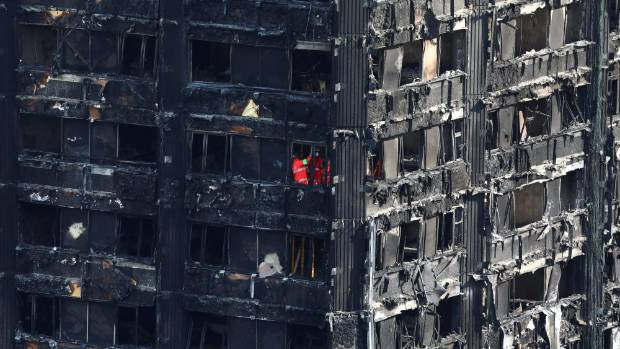 Members of the emergency services work inside the burnt-out remains of the Grenfell apartment tower.