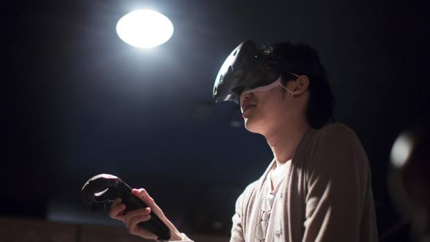 TOKYO, JAPAN - MAY 12:  A visitor wearing an HTC Corp. Vive VR headset plays the Salomon's Carpet VR virtual reality ...