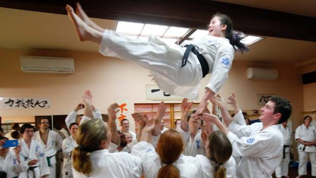 Aria Cressy is tossed into the air by fellow black belts after her successful grading.