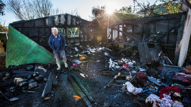Chris Gibbins inspects the remains of his shed, after a fire broke out in the early hours of the morning.