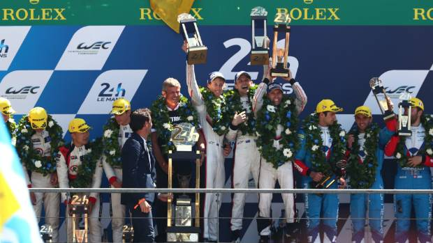 Kiwis Brendon Hartley, left, and Earl Bamber, and German team-mate Timo Bernhard celebrate winning Le Mans 24 Hour Race.