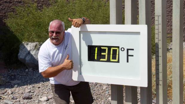 A man poses in front of a Death Valley temperature gauge. It's about 54 degrees Celsius at the time the picture was taken.