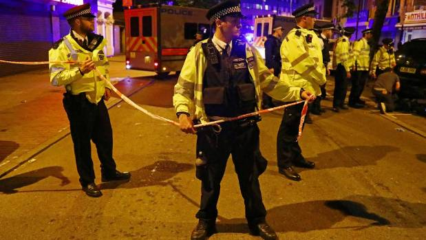 Police officers attend to the scene after a vehicle collided with pedestrians near the Finsbury Park Mosque.