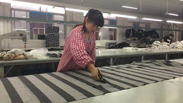 A young woman cuts fabric at Wuxi Everbright.