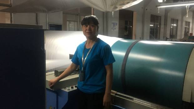 Guangyu Textile Factory, where workers like this one guard machines making fabrics for Westerners clothes.