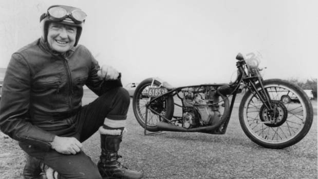 Burt Munro crouches next to his motorbike.