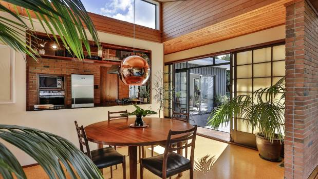 Original rimu sarking and Japanese-style shoji doors feature in this Mid-century gem for sale in Titirangi.