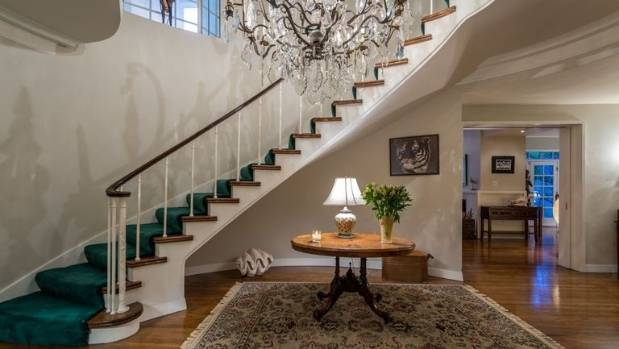 A large chandelier hangs in front of a sweeping staircase in the formal foyer.