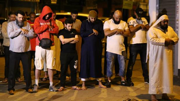 Men pray near the scene of the attack after it took place.