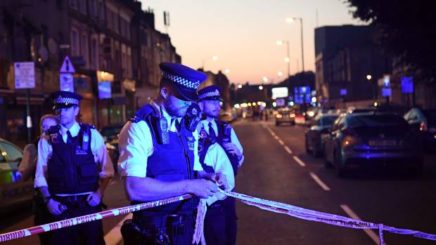 Police officers guard a road leading to Finsbury Park Mosque the attack.