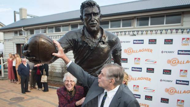 Sir Colin Meads touches the rugby ball his statue holds after its unveiling, as Dame Verna looks on at Te Kuiti on Monday.