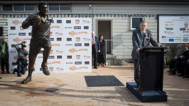 Colin Meads speaks alongside his imposing striding statue .
