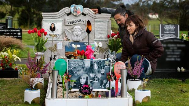Carlos and Alex Vergara at the graveside of their daughter, where a park bench was stolen.