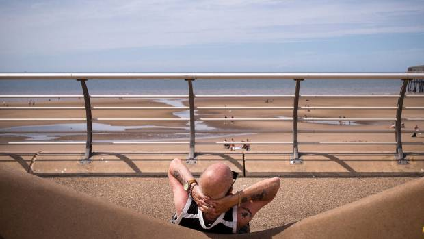 A man basks in the sun and heat on the Blackpool Promenade in Blackpool, England, where temperatures are expected to ...