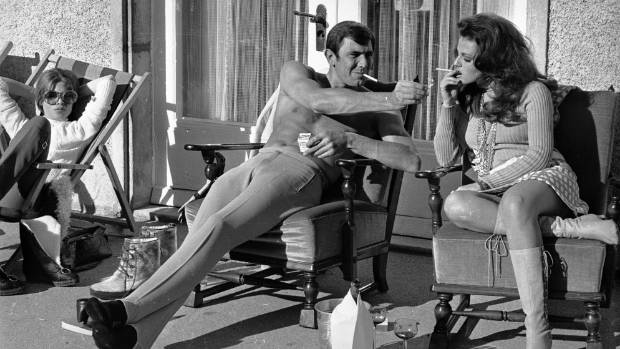 Stripped to the waist, Australian actor George Lazenby offers co-star Helena Ronee a light, whilst filming the James ...