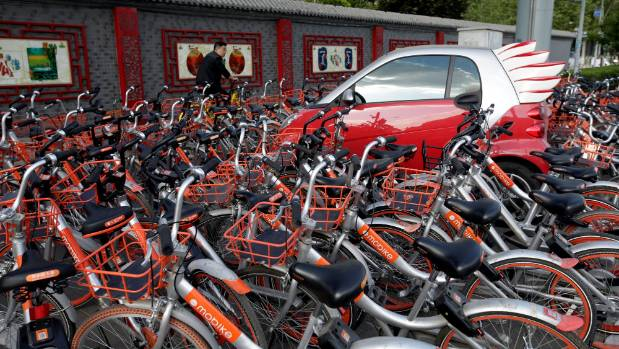 Mobike's shared bikes are parked around a car in Beijing.