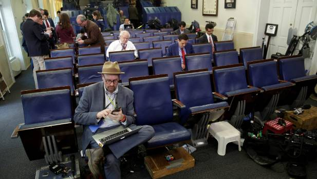 Glenn Thrush (front), chief White House political correspondent for the The New York Times, works in the briefing room ...