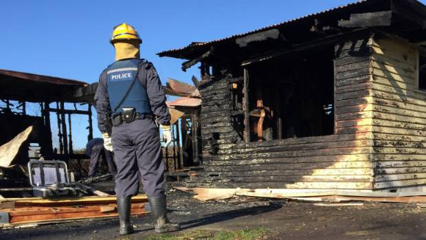A police officer inspects the remains of the house on Colin White Rd, Te Hauke, south of Hastings.