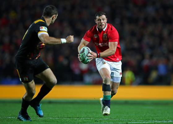 Robbie Henshaw of the Lions runs at Chiefs captain Stephen Donald.